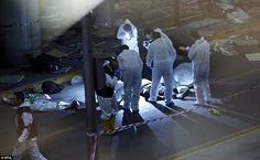 Crime scene investigators work next to a body after a suicide bomb attack killed dozens of...