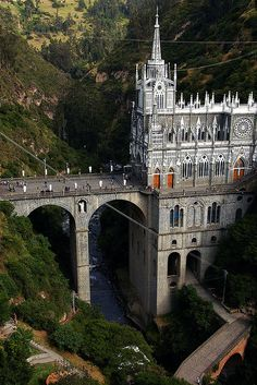 Santuario de Las Lajas, Colombia is a church perched on top of a mountain connected to another mountain by a bridge.