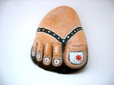 Foot in flip flop painted on stone.