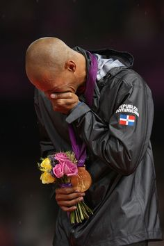 Felix Sanchez of the Dominican Republic is overcome with joy at the medal ceremony. He won gold in the  400m hurdles.