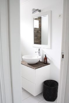 IKEA cabinet for bathroom with reclaimed wood planks for countertop. Vessel sink and industrial light fixture.
