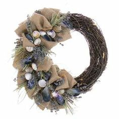 """Artful on its own or anchoring a beach-chic vignette, this eye-catching wreath features a twig base with lavender, grass, seashells, and burlap. Place a pillar candle in its center for a seaside-worthy centerpiece at your next soiree.  Product: WreathConstruction Material: Silicone and twigsColor: MultiFeatures: Includes lavender, grass, seashells and natural burlapDimensions: 19"""" Diameter"""