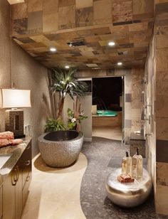 spa bathroom w/ a stone soaking tub and natural stone tiles via cornerstone architects