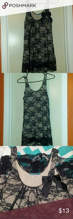 Lace Tank Top The black lace tank top is lined with a nude, soft material. The bow adds a nice touch to the top. Perfect for many different occasions. You can dress it up or keep it super casual. No rips or tares in the lace! Julie's Closet Tops Tank Tops