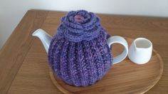 Purple hand knitted tea cosy with a crochet flower by DottyKnits