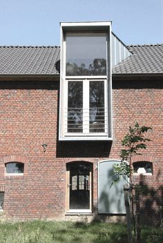 Architect Jeanne Dekkers has renovated and extended a brick farmhouse in the Dutch village of Banholt, adding contemporary additions clad in horizontal spruce battens that enclose a cobbled courtyard.