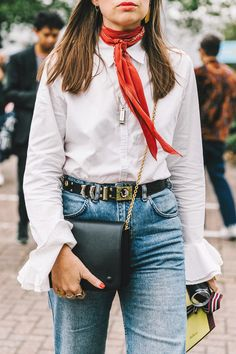 London Fashion Week Street Style - Neckerchief scarf, white button-down blouse with bell sleeves, faded vintage jeans, embellished belt, and chain mini bag.