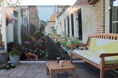 Een tuindoek met een doorkijk geeft de illusie dat je tuin groter is. Hier een voorbeeld van een klant die ons dit voorbeeld toestuurde. Een simpele maar fraaie oplossing om die saaie stenen muur weg te werken.