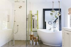 Subtle Soak~The master bath, designed by Kim Lewis, balances geometric motifs (including a wall tile by Ann Sacks) and elements from nature. Silver-armed wall sconces by Rejuvenation; Abrazo freestanding tub by Kohler.