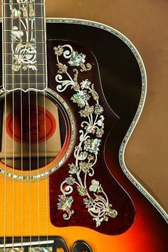 Here we have one of the most beautiful guitars you will ever see! A Gibson SJ-200 Masterpiece Custom acoustic guitar.This is definitely not your typical SJ-200. The inlay work of pearl and abalone is very ornate. These are not your typical inlays. These are some of the finest you will see on a gu... #beautifulguitars #customguitars