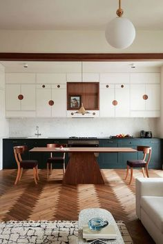 stunning mid-century inspired open kitchen with herringbone floors and circle details | polish prewar apartment tour on coco kelley #interiordesigners