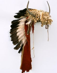 Buffalo Horn Bonnet, Crow or Arikara. ДА2. Date: 1860. Width of cap: 9 in. Catherine Bradford McClellan Collection.  Horn headdress - red wool cloth spine with tanned hide skull cap. Hawk feathers and split buffalo horns attached to skull piece with overlay bead decoration across front band with red string tassles on each side. Eagle feathers down center of trailer. Buffalo Bill Center of West.