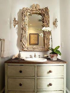 O espelho do lavabo tem uma moldura de galhos secos