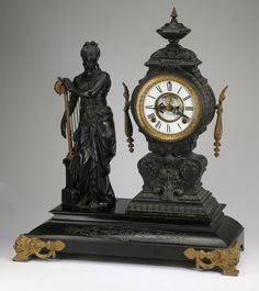 """Figural mantel clock by the Ansonia Clock Company, late 19th century, executed in bronze, the clock with Roman dial within a gilt and foliate banded body, flanked by a standing maiden in Grecian dress with a gilt harp, the whole on a incised black enameled base, 22""""h x 19.5""""w x 8.5""""d."""