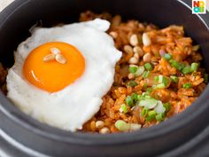30-minute recipe for kimchi fried rice, served with a fried sunny side up egg and roasted pine nuts.
