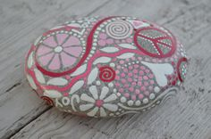 Love, Joy, Peace, Bliss are the words hidden in the swirls & dots on this gorgeous Pink & White Inspiration rock. A beautiful one of a kind meditation rock or just a wonderful paper weight or piece of Art. Truly a unique conversation piece. Will bring a smile to anyones face. A very positive piece for sure. This rock measures approx 4.5x3x1 and has a coat of varnish to seal and protect, Enjoy! INTERNATIONAL ORDERS..are charged for shipment by boat. (4 weeks minimum travel time) If you would…