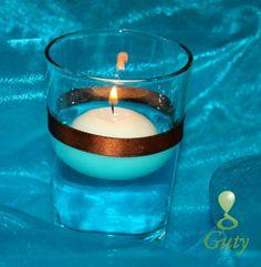 Svietnik s farebnou vodou, stuhou a plávajúcou sviečkou.