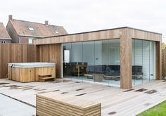 Moderne relaxruimte in afrormosia hardhout. Totaalafwerking: polierbeton binnenin, wandisolatie en gyprocafwerking. Terras buiten in IPE hardhout.