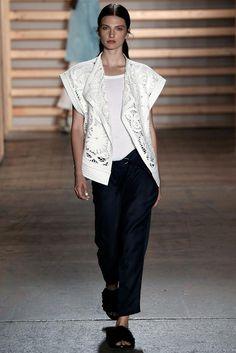 Tibi Spring 2015: A white crochet moto vest with black pants and black fringe flat slides.
