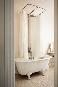 oh I die! lovely old white claw foot vintage bath tub with shower over and old towel rail and curtain, loving the white floor tiles and light xx