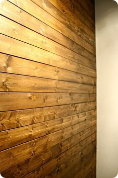 Wood Plank Wall - she used pine planks rather than pallets making this project a WHOLE lot easier. Stained with dark walnut stain. LOVE.