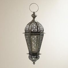 "Enhance the dramatic beauty of your sitting room with our 23"" Filigree Overlay Lantern. Handcrafted of glass and metal with antique zinc finish, this beautiful lantern features intricate filigree overlay on the glass to cast delicate shadow patterns on the walls when lit."