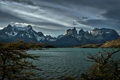 Photograph by Stuart Litoff.  #Trees frame #LakePehoe and the #CuernosDelPaine #mountains in #TorresDelPaine #NationalPark, in the #Patagonia region of #Chile.