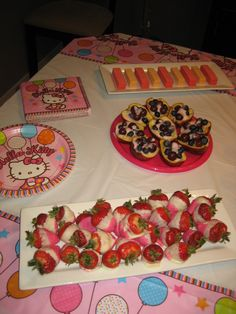 Wafer cookies, apple cups filled with strawberry yogurt, grapes and blueberries and white chocolate covered strawberries with pink sprinkles.
