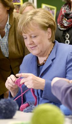German chancellor Angela Merkel crochets during a visit to the multi-generational house 'Dorflinde' in Langenfeld, southern Germany