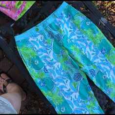 """Lilly Pulitzer beach Vacation  Capris These are loaded with charm.  Two playful prints. Have been paired together in shades of blues and greens with white and yellow accents.  The sword fish pattern is bold and compliments the lazy beachside umbrella scene on the other print.   White eyelet lace edging finishes off the hem.  Flat front with a chino style button back pocket.  Some stretch for a nicer fit, too.  Size 8.  Waist measures 15.5"""". Inseam is 19.5"""". Super cute and very nice condition…"""