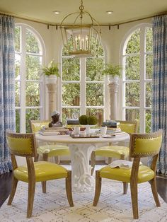 Love the yellow leather on these chairs... perfectly paired with blue and white curtains! Notice they continued hardward all the way around.