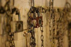 Jáchymovský uranový důl - U stropu ve špinavé části šatny se na takzvaných strašácích (hácích) houpou pracovní šaty. Ke každému strašákovi vede řetízek zajištěný proti spuštění nenechavci zámečkem.