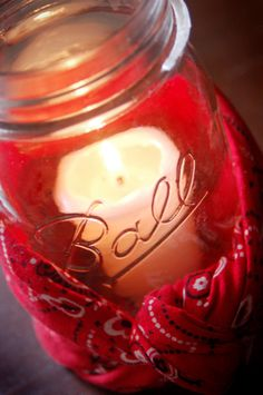 Small citronella candles inside clear mason jars with red bandanas around the base of the jars.