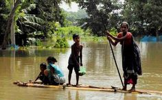 A woman along with her children moves to safety with the help of a banana raft at a flooded village in Kamrup district of Assam. (PTI) Assam floods, July 2013 Posted by floodlist.com