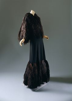 "With the introduction of her couture shop to the Parisian fashion radar in 1914, Gabrielle ""Coco"" Chanel seemingly created an entirely new female fashion persona. Her oeuvre catered to idyllic comfort and moveability, while her finishing techniques and intentionally ostentatious accessory items provided the Parisian upper classes a fashionable exclusivity. This gown and matching evening cape, is constructed from Chanel's signature black silk crêpe and  combed ostrich feathers  1933-35"
