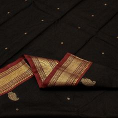 The body of this #Kanjivaram is like a star-studded velvet sky on a dark night. The black #silk body is sprinkled with glistening gold buttis. The contrast border in chilly red is embellished with a gold wave pattern and the mystical rudraksh motif, which flows gently into the eye-catching pallu in a riot of red. An offering from Sarangi's black Kanjivarams. Code 390124982.