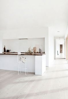Minimalistic kitchen with white walls and hardwood flooring.