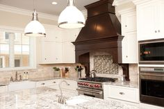 A dramatic range hood draws the eye in this home from Oakley Home Builders
