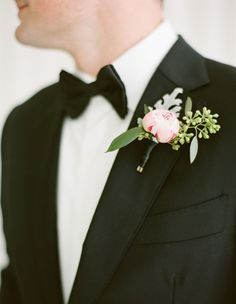Wrapped in tuxedo black satin, an un-unopened peony and textured greens brought color to a traditional suit.