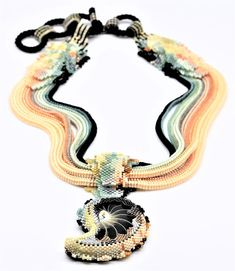 I hand beaded this gorgeous collar-style necklace by using tiny Japanese glass seed beads in sea green, peach, teal, jonquil, rainbow blue, silver lined squash, orange, shell pink, pearl grey, cream matte black, metallic hematite. As a focal peace I used natural Nautilus Shell ( with