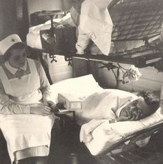 Nurse in the interior of a railway carriage, most likely in the WWII era (please check source)