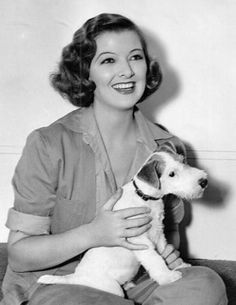 Myrna Loy holding a Wire Fox Terrier (though, it does not appear to be Asta from The Thin Man series).