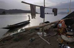 A woman cooks food at her makeshift tent on a road near the flood-destroyed houses at Tin Tukra, Guwahati on Saturday.(AP) Assam floods, July 2013 Posted by floodlist.com