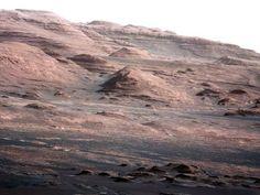 """O robô Curiosity, da Nasa, enviou as primeiras imagens a cor e em alta resolução do Mount Sharp, situado no centro da cratera Gale, onde o veículo aterrisou em Marte. A montanha, com 5,5 quilômetros de altura, tem intrigado os cientistas por uma peculiaridade geológica que têm chamado de """"Grand Canyon ao contrário"""". As camadas rochosas mais perto do cume são inclinadas em relação às que se encontram por baixo."""