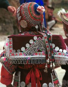 Jpeg 141K Iron beating Miao festival costume in miniature worn by one of little girls who danced for us in Gao Zhai village, Bai Jin township, Huishui county, Guizhou province. She is wearing what looks like a very ornate baby carrier on her back. Note the finely gathered hat crown worn by the little girl and shown in closeup in photos further down in the photo gallery. I bought one of these beautifully made hats for my collection 0110C23
