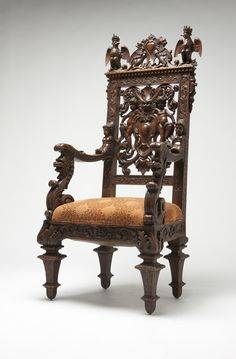 An elaborately carved and figured Victorian Renaissance Revival hall chair. Second half 19th century, walnut, the horizontal crestrail centering addorsed griffins flanked by crowned eagles above a pierced back with cherubs supporting a shield and lion's mask between foliate carved stiles joined to female sphinx-mounted arms with foliate scroll terminals on leonine uprights over a shaped padded seat with an acanthus and scrolling vine carved seatrail, on square tapering leg.