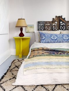 a bedroom in the home of Holly in Toronto, Canada, as depicted in Covet Garden magazine -- the headboard is repurposed latticework from the porch of a Victorian home demolished in Detroit, Michigan.