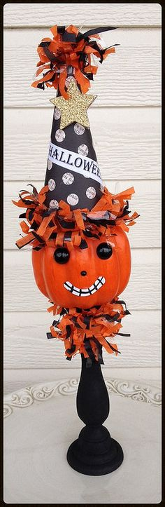 A cute jack o lantern is wearing a snazzy party hat with a golden star and tissue trim.. He sits atop a wooden candlestick and is ready for some fun.