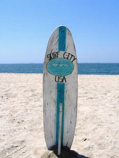 Surf City, USA Surf Board standing up in the sand.