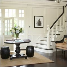 Double high wainscoting to include the windows around the doors. When carried up the stairs on the horizontal feels natural.    I love the dark wood tones and crisp white walls.
